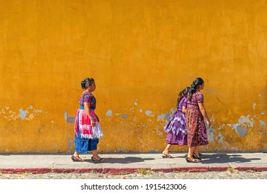 ANTIGUA, GUATEMALA - MARCH 29, 2013: Guatemalan maya indigenous women walking in front of a colonial facade of Antigua city.