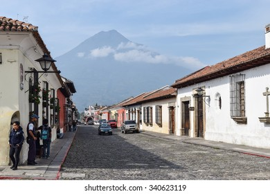 Antigua, Guatemala May 30, 2015: Typical street scene in Spanish colonial town of Antigua, Guatemala, a UNESCO World Heritage Site founded in the 16th century. Aqua volcano is in the background.