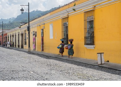 Antigua Guatemala, Guatemala - October 05 2019: Two women walk down a street carrying a basket of fruits on their head.