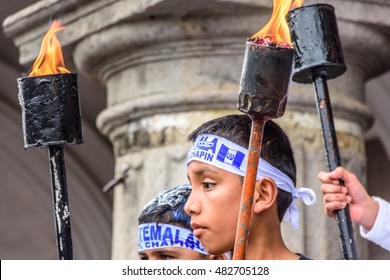 Antigua, Guatemala - September 14, 2015: Patriotic boys hold lit torches outside city hall during Guatemalan Independence Day celebrations