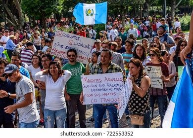 Antigua, Guatemala - September 15, 2017: Locals wave Guatemalan flags & slogans protesting against government corruption in front of city hall on Guatemala's Independence Day.