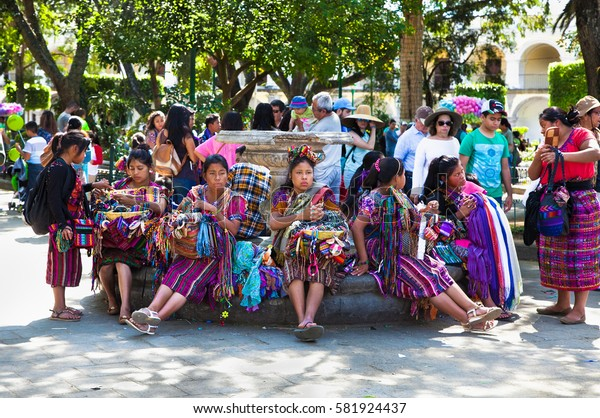 ANTIGUA, GUATEMALA-DEC 27, 2015: : Guatamalian woman selling traditional  colorful fabric and goods at the street in Antigua, on Dec 27, 2015, Guatemala.