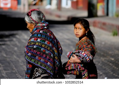 Antigua/Guatemala - 05 15 2015  Guatemalan old woman and her granddaughter were in their traditional dress. Its early morning and they were walking in the streets to gether