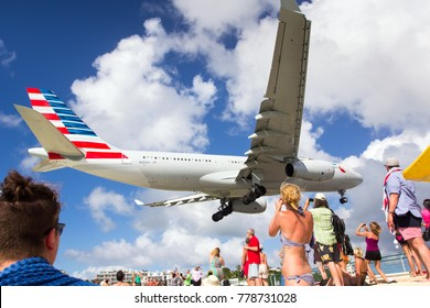 ANTILLES, PHILIPSBURG / ST. MAARTEN (SAINT-MARTIN) - PRINCESS JULIANA AIRPORT. AUGUST 15, 2017. Passenger plane Airbus A330 of American Airlines flies low over the Maho Beach and leisure tourists.