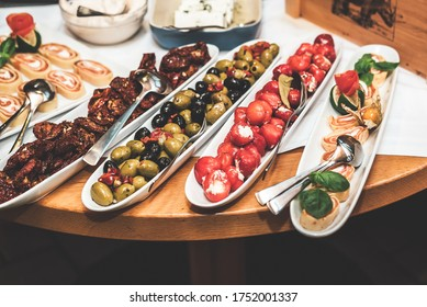 Antipasti appetizer sweet cherry peppers stuffed with soft cheese, olives with oil, dried tomatoes and cheese rolls. White oblong ceramic dishes on wooden table.Celebration, party, birthday or wedding