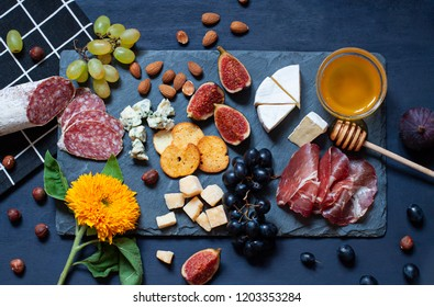Antipasti food dark blue flat lay with nuts, honey, cured meat, salami, cheeses, grapes and figs. Top view snack concept composition
