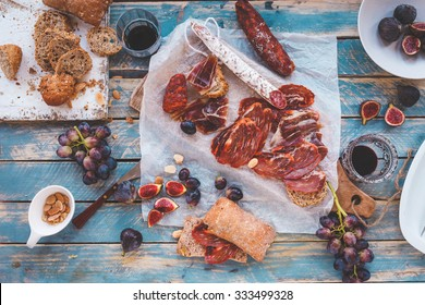 Antipasti and fruit concept. Tasting gourmet party on a rustic wooden table. A quick and easy snack for party time. Rustic style.