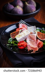 Antipasti plate with fresh figs, cheese and prosciutto