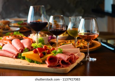 Antipasti platter with different meat and cheese products on wooden board
