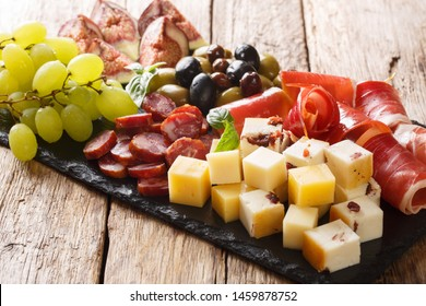 Antipasti snack plate of cheese, prosciutto ham, grapes, figs, sausages and olives close-up on a wooden table. horizontal