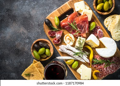 Antipasto board with sliced meat, ham, salami, cheese, olives and red wine. Top view with copy space.