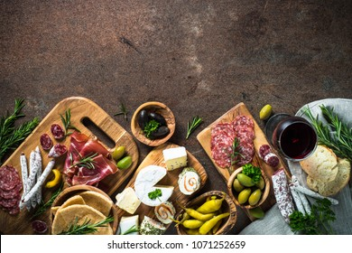Antipasto delicatessen - sliced meat, ham, salami, cheese, olives, ciabatta and red wine on dark stone table. Top view with space for text.