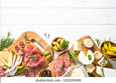 Antipasto delicatessen - sliced meat, ham, salami, cheese, olives, ciabatta and pepperoni on white wooden table. Top view with copy space.