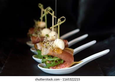 antipasto - Italian cold snack from a ham or Parma ham with figs, mozzarella and cedar nuts. Seasoned salad with balsamic sauce and liquid honey