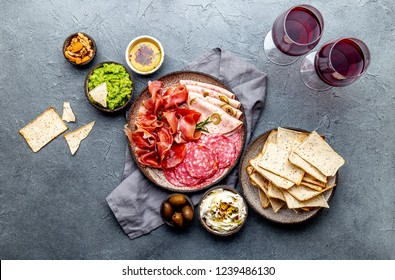 Antipasto. Meat platter, chips and sauces, red wine on gray background. Top view.