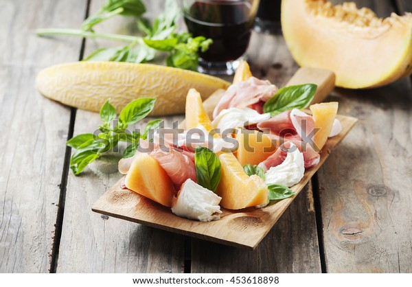 Antipasto with melon, mozzarella, ham and basil, selective focus