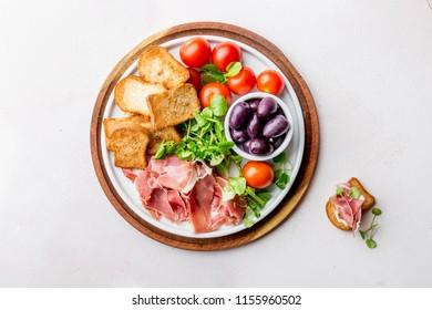 Antipasto Plate with dried bread, ham serrano, tomato cherry and purple olives. White background