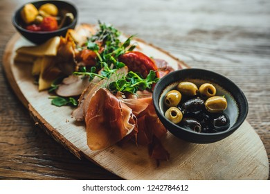 Antipasto plate with dry ham, jerky, salami, cheese and grapes on a wooden background