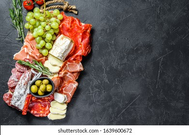 Antipasto platter cold meat with grapes, prosciutto, slices ham, beef jerky, chorizo salami, fuet, Camembert and goat cheese. Black background. Top view. Copy space