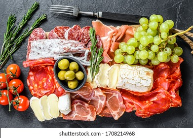 Antipasto platter cold meat with grapes, prosciutto, slices ham, beef jerky, chorizo salami, fuet, Camembert and goat cheese. Black background. Top view