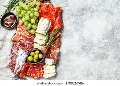 Antipasto platter cold meat with grapes, prosciutto, slices ham, beef jerky, chorizo salami, fuet, Camembert and goat cheese. Gray background. Top view. Copy space