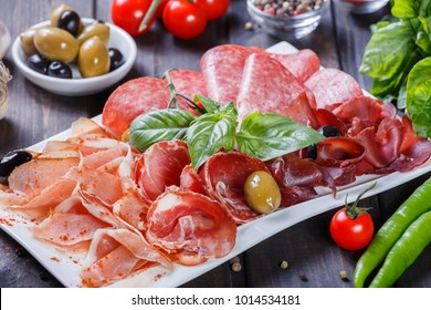 Antipasto platter cold meat plate with prosciutto, slices ham, salami, decorated with basil and olive on wooden background. Meat appetizer