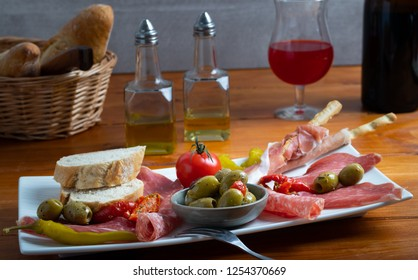 Antipasto platter a cold meat plate with prosciutto, slice of ham,salami, decorated with olives,dried tomatoes and green peppers on a wooden background.