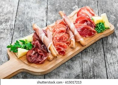 Antipasto platter cold meat plate with grissini bread sticks, prosciutto, slices ham, beef jerky, salami and arugula on cutting board on wooden background. Meat appetizer