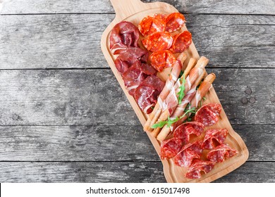 Antipasto platter cold meat plate with grissini bread sticks, prosciutto, slices ham, beef jerky, salami and arugula on cutting board on wooden background. Meat appetizer. Top view