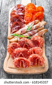 Antipasto platter cold meat plate with grissini bread sticks, prosciutto, slices ham, beef jerky, salami and arugula on cutting board on wooden background close up. Meat appetizer