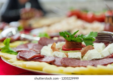 Antipasto platter with flat sausage, slices yellow cheese, white cheese, decorated with parsley and red pepper ring. Appetizer.