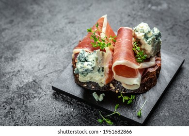 Antipasto platter with jamon, prosciutto, blue cheese, Appetizers. meat snacks for red wine. Appetizer on a slate board.