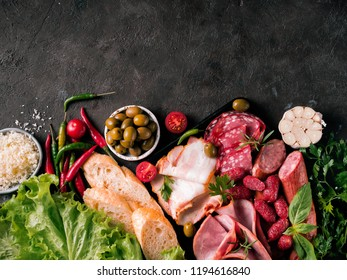 Antipasto set platter on black stone background. Cold smoked meat plate with sausage,sliced ham, bacon, olives, bread, cheese and herbs. Appetizer variety with copy space. Top view or flat lay