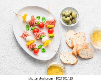Antipasto skewers. Mediterranean appetizer to wine - prosciutto, bell peppers, cherry tomatoes, mozzarella cheese on skewers and white wine. Delicious snack with wine, tapas on a light background