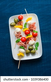 Antipasto skewers. Mediterranean appetizer to wine - prosciutto, bell peppers, cherry tomatoes, mozzarella cheese on skewers. Delicious snack with wine, tapas on a blue background, top view