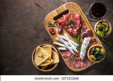 Antipasto - sliced meat, ham, salami, olives and glass wine on dark stone table. Top view with space for text.
