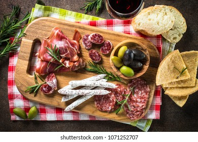 Antipasto - sliced meat, ham, salami, olives on dark stone table. Top view.