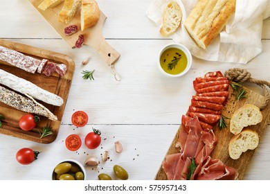 Antipasto with traditional Spanish meat snacks on wooden board and white wooden background.