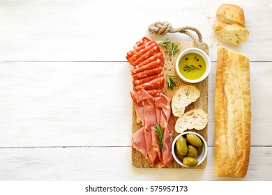 Antipasto with traditional Spanish meat snacks on wooden board and white wooden background