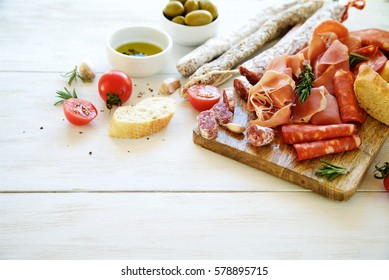 Antipasto with traditional Spanish meat snacks on wooden board and white wooden background. Copy space.