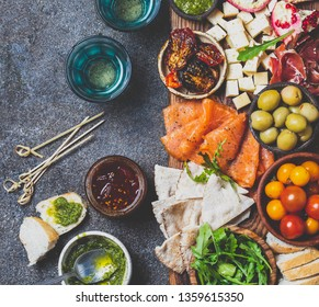 Antipasto. Wine set appetizer. Ham serrano, smoked salmon, dried and fresh tomatoes olive cheese, wine on board. Top view, gray cncrete background