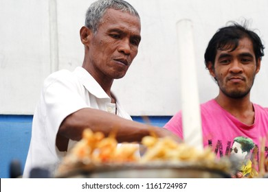 Antipolo City, Philippines: August 18, 2018 - A street food vendor cooks food on his street food cart.