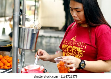 Antipolo City, Philippines - August 18, 2018: A woman eats street food at a street food cart.