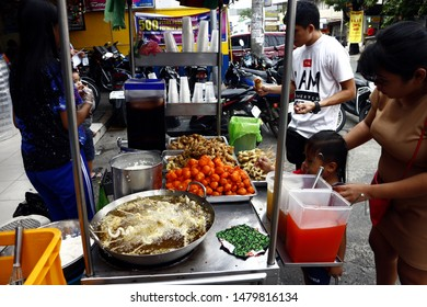 ANTIPOLO CITY, PHILIPPINES – AUGUST 8, 2019: Customers buy assorted street food at a street food cart along a busy street.