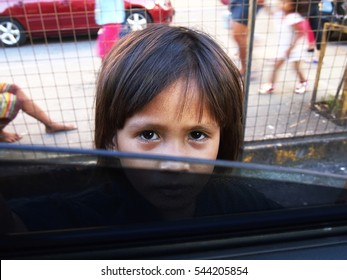 ANTIPOLO CITY, PHILIPPINES - DECEMBER 19, 2016: A child looks into a car window asking for some money.