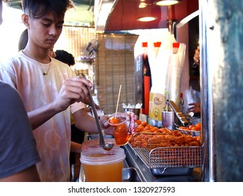 ANTIPOLO CITY, PHILIPPINES - FEBRUARY 21, 2019: A customer buys snack food from a food cart at a public park.