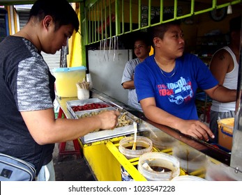 ANTIPOLO CITY, PHILIPPINES - FEBRUARY 3, 2018: Customers of a snack food kiosk pick their choice of fried food.