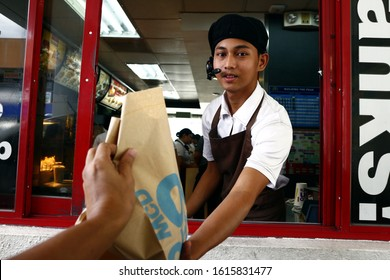 Antipolo City, Philippines - January 11, 2020: Worker at a fast food restaurant give the food order of a customer at a drive thru window.