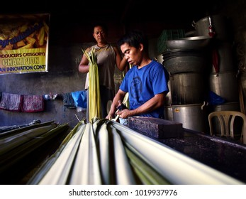 ANTIPOLO CITY, PHILIPPINES - JANUARY 26, 2018: Men prepare to cook a local delicacy called Suman or steamed glutenous rice.