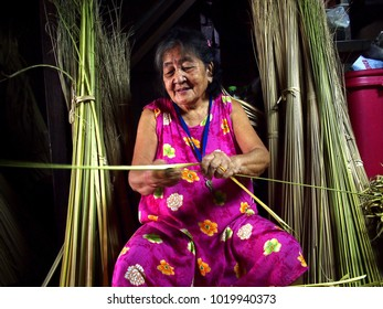 ANTIPOLO CITY, PHILIPPINES - JANUARY 26, 2018: An elderly lady trims coconut tree leaves to be used as packaging for a local delicacy called Suman or steamed glutenous rice.